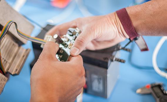 Detailaufnahme zur Realisierung von Hardwarelösungen. Zwei Hände halten eine Platine.