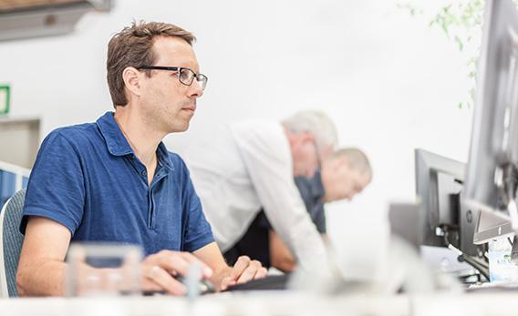 Ein Mitarbeiter arbeitet am Laptop. Im Hintergrund arbeiten zwei weitere Mitarbeiter an einem Projekt.