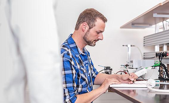 Ein Mitarbeiter notiert sich die generierten Ergebnisse aus den Testverfahren.
